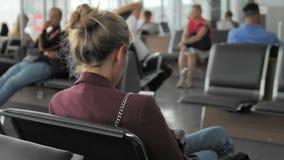Παραγνωρισμένα νέα θηλυκά κοινωνικά δίκτυα χρήσεων στο smartphone της περιμένοντας μια πτήση καθμένος στον αερολιμένα απόθεμα βίντεο