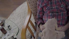 Παραγνωρισμένο μικρό αγόρι που ταλαντεύεται στην καρέκλα του, που κρατά ένα μαλακό παιχνίδι στα χέρια του κοντά επάνω φιλμ μικρού μήκους
