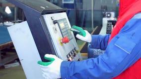 Παραγωγή γραμμών των πλαστικών παραθύρων Εργαζόμενος στο εργαστήριο ο εργαζόμενος χτυπά στα κουμπιά για το επιθυμητό πρόγραμμα φιλμ μικρού μήκους