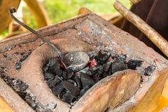 Παραγωγή κέρατων σιδηρουργών γερακιών των όπλων που λειώνουν θέρμανσης μετάλλων τον καίγοντας κάδο κουταλιών ανθράκων κόκκινο σφυ στοκ φωτογραφίες