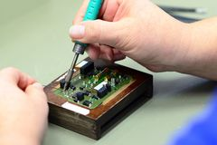 Παραγωγή και συνέλευση της μικροηλεκτρονικής σε ένα εργοστάσιο υψηλής τεχνολογίας - συγκολλώντας σίδηρος στοκ φωτογραφίες