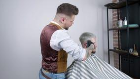 Παραγωγή του κουρέματος Νέο γενειοφόρο άτομο που παίρνει το κούρεμα από τον κουρέα καθμένος στην καρέκλα στο barbershop απόθεμα βίντεο