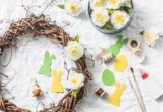 Παραγωγή του σπιτικού στεφανιού Πάσχας των αμπέλων με τα λουλούδια, κουνέλια εγγράφου, κορδέλλες σε ένα άσπρο υπόβαθρο, τοπ άποψη στοκ φωτογραφία με δικαίωμα ελεύθερης χρήσης