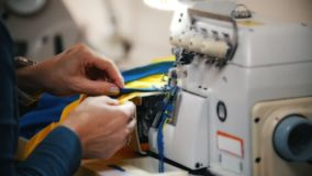 Παραγωγή των ενδυμάτων Θηλυκή εργασία χεριών για τη ράβοντας μηχανή στο στούντιο Κλείστε αυξημένος απόθεμα βίντεο