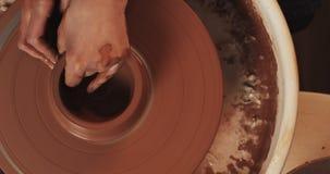 Ο αγγειοπλάστης κάνει την αγγειοπλαστική από στενό επάνω αργίλου Παραγωγή των κεραμικών προϊόντων από τον κόκκινο άργιλο Στριμμέν απόθεμα βίντεο