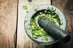 Παραγωγή φρέσκου Pesto στο κονίαμα και το γουδοχέρι Στοκ Φωτογραφίες