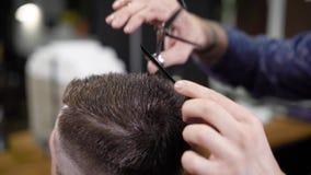 Παραγωγή hairstyle με το ψαλίδι και τη χτένα Κομμωτής στην εργασία Αρσενικοί πελάτης και κουρέας Κλείστε επάνω την όψη φιλμ μικρού μήκους