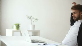 Παραγωγικός ικανοποιημένος επιχειρηματίας που κλίνει την πίσω εργασία γραφείων λήξης για το lap-top φιλμ μικρού μήκους