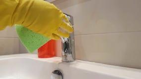 Παραδίδει τα γάντια πλένει το νεροχύτη καθαρό στο κεραμικό πλύσιμο λουτρών απόθεμα βίντεο