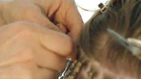 Παραδοσιακά αφρικανικά hairstyles στις λευκές γυναίκες ο επαγγελματικός κομμωτής υφαίνει τις κοτσίδες φιλμ μικρού μήκους