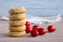 Παραδοσιακά ελληνικά μπισκότα Πάσχας με τους σπόρους σουσαμιού και τα χρωματισμένα αυγά στοκ εικόνα