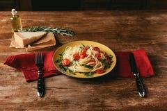 παραδοσιακά ζυμαρικά με τις ντομάτες και arugula στο πιάτο στον πίνακα με την παρμεζάνα Στοκ Εικόνες