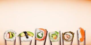 Παραδοσιακά ιαπωνικά κομμάτια σουσιών που τοποθετούνται μεταξύ chopsticks στο υπόβαθρο χρώματος κρητιδογραφιών Στοκ Φωτογραφίες