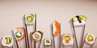 Παραδοσιακά ιαπωνικά κομμάτια σουσιών που τοποθετούνται μεταξύ chopsticks στο υπόβαθρο χρώματος κρητιδογραφιών Στοκ Εικόνα