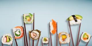 Παραδοσιακά ιαπωνικά κομμάτια σουσιών που τοποθετούνται μεταξύ chopsticks, που χωρίζονται στο ανοικτό μπλε υπόβαθρο κρητιδογραφιώ Στοκ εικόνες με δικαίωμα ελεύθερης χρήσης