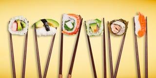 Παραδοσιακά ιαπωνικά κομμάτια σουσιών που τοποθετούνται μεταξύ chopsticks, που χωρίζονται στο ανοικτό μπλε υπόβαθρο κρητιδογραφιώ Στοκ Φωτογραφίες