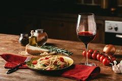 παραδοσιακά ιταλικά ζυμαρικά με τις ντομάτες και arugula στο πιάτο και το γυαλί Στοκ Εικόνες