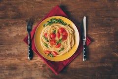 παραδοσιακά ιταλικά ζυμαρικά με τις ντομάτες και arugula στο πιάτο με το μαχαίρι και το δίκρανο Στοκ φωτογραφία με δικαίωμα ελεύθερης χρήσης