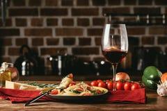 παραδοσιακά ιταλικά ζυμαρικά με τις ντομάτες και arugula στο πιάτο και το γυαλί Στοκ φωτογραφία με δικαίωμα ελεύθερης χρήσης
