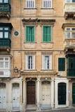 Παραδοσιακά μπαλκόνια, πόρτες και παράθυρα σε έναν κατοικημένο φραγμό των διαμερισμάτων σε Valletta, Μάλτα στοκ φωτογραφία