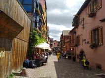 Παραδοσιακά σπίτια με τις ζωηρόχρωμες προσόψεις και κεκλιμένες στέγες σε Riquewihr, Γαλλία στοκ φωτογραφίες
