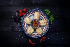 Παραδοσιακές βρασμένες στον ατμό μπουλέττες Manti στο πιάτο με την ασιατική διακόσμηση με τη σάλτσα ντοματών Τοπ όψη σκοτεινός ξύ Στοκ Φωτογραφία
