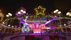 Παραδοσιακή αγορά Χριστουγέννων, άνθρωποι τουριστών που απολαμβάνει τις χειμερινές διακοπές σε φωτισμένο Ñ  arousel κοντά στο νέ απόθεμα βίντεο