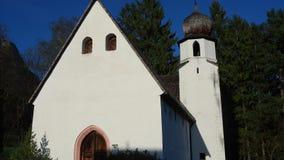 Παραδοσιακή αυστριακή εκκλησία στο περιβάλλον βουνών απόθεμα βίντεο