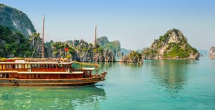 Παραδοσιακή βάρκα που πλέει στα πράσινα νερά μεταξύ των νησιών βράχου του κόλπου Βιετνάμ Halong στοκ φωτογραφίες