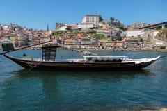 Παραδοσιακή βάρκα Rabelo στις όχθεις του ποταμού Douro και των ζωηρόχρωμων προσόψεων των χαρακτηριστικών σπιτιών Πόρτο, Πορτογαλί Στοκ φωτογραφία με δικαίωμα ελεύθερης χρήσης
