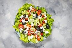 Παραδοσιακή ελληνική σαλάτα με τα φρέσκα λαχανικά, το τυρί φέτας και τις ελιές στο συγκεκριμένο υπόβαθρο Τοπ όψη στοκ εικόνες