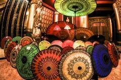 Παραδοσιακή ζωηρόχρωμη ανοιγμένη ασιατική ομπρέλα που τοποθετούνται στο επίγειο ασιατικό ταξίδι στοκ εικόνα