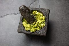 Παραδοσιακή λατινοαμερικάνικη μεξικάνικη σάλτσα guacamole στο κονίαμα πετρών, γκρίζο υπόβαθρο πλακών στοκ φωτογραφίες