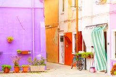 Παραδοσιακοί ζωηρόχρωμοι τοίχοι των κοινών παλαιών σπιτιών με τα δοχεία λουλουδιών και το ποδήλατο κοντά στην πόρτα εισόδων στο ν Στοκ φωτογραφία με δικαίωμα ελεύθερης χρήσης