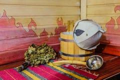 Παραδοσιακός ρωσικός εξοπλισμός λουτρών στον ξύλινο πάγκο Ξύλινος κάδος, κουτάλα, δρύινη σκούπα, καπέλο λουτρών και πετσέτα Στοκ Εικόνα