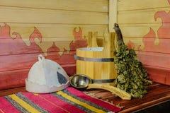 Παραδοσιακός ρωσικός εξοπλισμός λουτρών στον ξύλινο πάγκο Ξύλινος κάδος, κουτάλα, δρύινη σκούπα, καπέλο λουτρών και πετσέτα Στοκ εικόνες με δικαίωμα ελεύθερης χρήσης