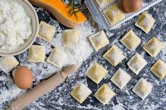 Παραδοσιακό ακατέργαστο ravioli με την κολοκύθα σε έναν ξύλινο πίνακα με το αλεύρι, χειροποίητη, διαδικασία μαγειρέματος στοκ εικόνες