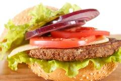 Παραδοσιακό αμερικανικό cheeseburger Το κρέας, το κουλούρι και τα λαχανικά κλείνουν επάνω στοκ εικόνες