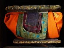 Παραδοσιακό αρχαίο θιβετιανό βιβλίο: τα κείμενα είναι τυλιγμένα στο πορτοκαλί ύφασμα, στην κορυφή και το κατώτατο σημείο είναι πα Στοκ εικόνες με δικαίωμα ελεύθερης χρήσης