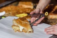 Παραδοσιακό βαλκανικό burek τροφίμων με την εκμετάλλευση χεριών τυριών και γυναικών με catcher τροφίμων στοκ εικόνα