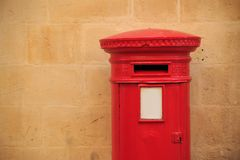 Παραδοσιακό, βρετανικό ταχυδρομικό κουτί στο κόκκινο χρώμα Ταχυδρομική θυρίδα που λαμβάνει τις επιστολές Ανοικτό πορτοκαλί τοίχος Στοκ Εικόνα