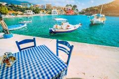 Παραδοσιακό ελληνικό εστιατόριο με τον μπλε και άσπρο πίνακα και καρέκλες στην παραλία του χωριού Assos κυανό ύδωρ στοκ φωτογραφία με δικαίωμα ελεύθερης χρήσης
