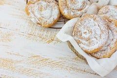 Παραδοσιακό ισπανικό ή φιλιππινέζικο ensaimada ζύμης Κονιοποιημένος στην ψύξη του ραφιού και στο ψάθινο καλάθι Άσπρος ξύλινος πίν στοκ εικόνες