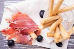 Παραδοσιακό ιταλικό grissini ραβδιών ψωμιού με το ζαμπόν prosciutto Στοκ Εικόνα