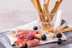 Παραδοσιακό ιταλικό grissini ραβδιών ψωμιού με το ζαμπόν prosciutto Στοκ Φωτογραφία