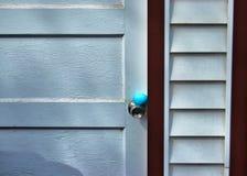 Παραδοσιακό κυνήγι αυγών Πάσχας στο κατώφλι Το μπλε αυγό είναι κρυμμένο doorknob της ξεπερασμένης εισόδου γκαράζ Στοκ Φωτογραφία