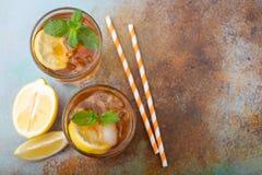 Παραδοσιακό παγωμένο τσάι με το λεμόνι, τη μέντα και τον πάγο στα ψηλά γυαλιά Δύο γυαλιά με το δροσερό θερινό ποτό στο παλαιό σκο Στοκ φωτογραφία με δικαίωμα ελεύθερης χρήσης