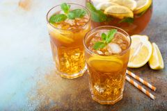 Παραδοσιακό παγωμένο τσάι με το λεμόνι, τη μέντα και τον πάγο στα ψηλά γυαλιά Δύο γυαλιά με το δροσερό θερινό ποτό στο παλαιό σκο Στοκ εικόνα με δικαίωμα ελεύθερης χρήσης