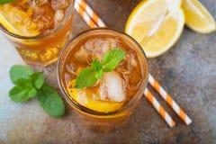 Παραδοσιακό παγωμένο τσάι με το λεμόνι, τη μέντα και τον πάγο στα ψηλά γυαλιά Δύο γυαλιά με το δροσερό θερινό ποτό στο παλαιό σκο Στοκ Φωτογραφία