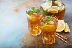 Παραδοσιακό παγωμένο τσάι με το λεμόνι, τη μέντα και τον πάγο στα ψηλά γυαλιά Δύο γυαλιά με το δροσερό θερινό ποτό παλαιό σε σκου Στοκ εικόνα με δικαίωμα ελεύθερης χρήσης